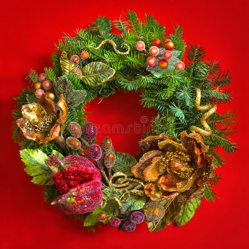 Christmas fir tree wreath over red background. Christmas fir tree wreath decorated with artificial flowers over red background royalty free stock photos