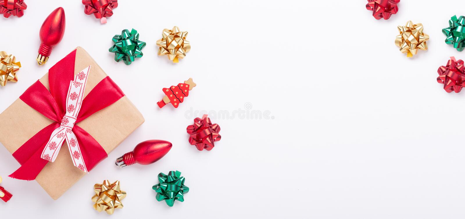 Christmas flat lay with present box and red, green, gold gifts and bows on white background stock photo
