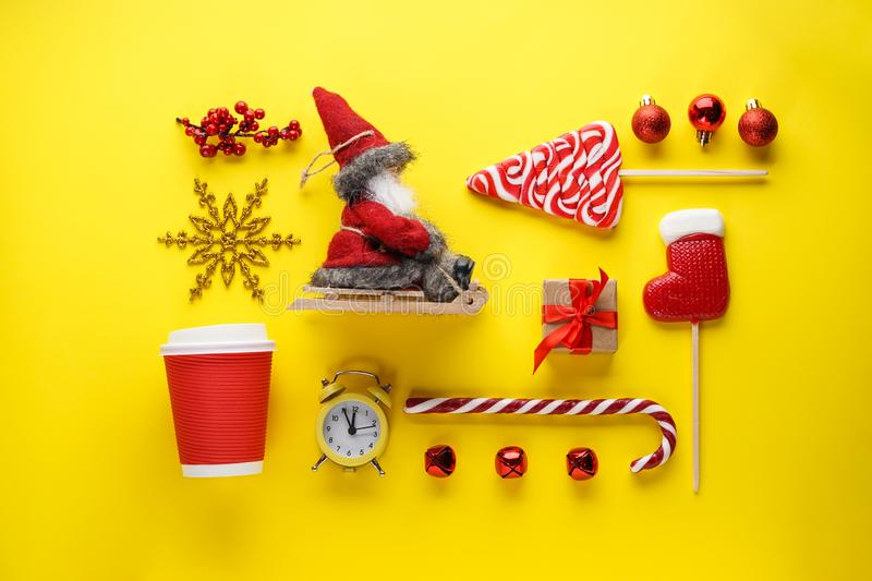 Christmas flat lay composition. Christmas sweets, gift, toys, Santa in a sleigh, an alarm clock with a cool down time and a cup on royalty free stock photo