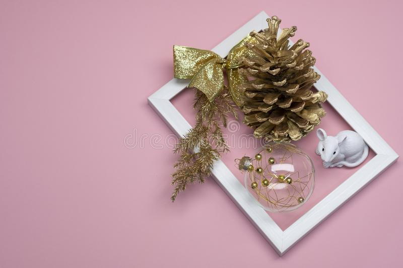 Christmas flat lay on pink background. In white frame, Golden cone, ball and white mouse. stock images