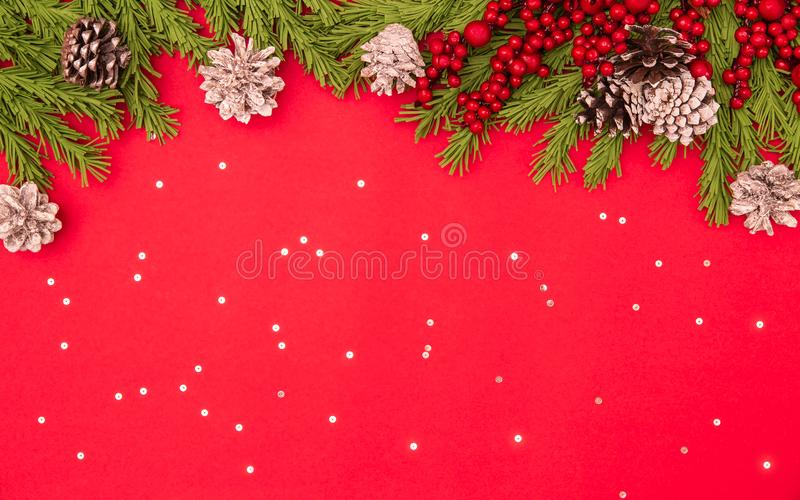 Christmas flat lay red background with fir branches, cones, holly berry, sparkles with copy space. Winter, New Year 2020, postcard. Social media concept royalty free stock photos