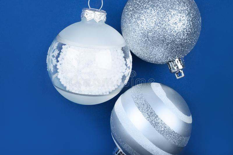 Christmas flatlay with baubles. Flatlay with white and silver Christmas baubles isolated on blue background royalty free stock photo