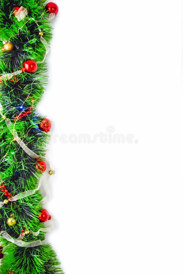 Green tinsel with red and gold balls on a white background. Christmas flatlay with green tinsel, red and gold balls, glowing lights and stars on a white royalty free stock images