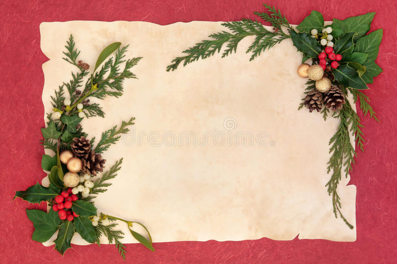 Christmas Floral Border. Christmas floral background border with gold baubles, holly and winter greenery over parchment and red background royalty free stock photos