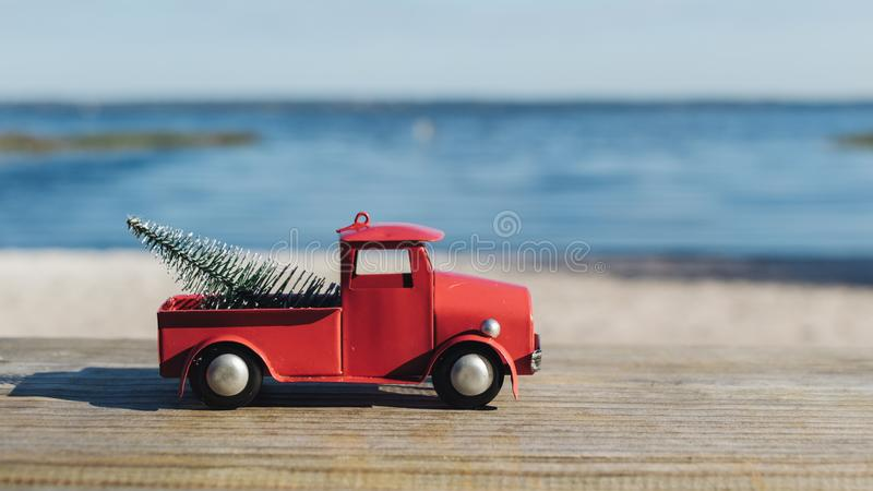 Christmas in Florida theme, red toy truck hauls a christmas tat Lake Louisa State Park in Clermont, Florida. Christmas in Florida concept, red craft truck hauls stock photo