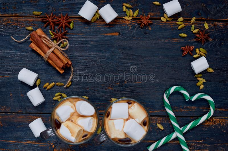 Christmas food background with copy space. Frame of hot chocolate with marshmallows, hearts of candy cones and winter spices stock photography