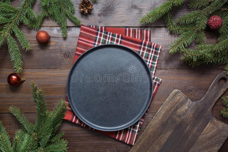 Christmas food border with black plate, evegreen branches, and red decor on wooden board. Space for text. Flat lay style. Christmas food border with black plate royalty free stock image