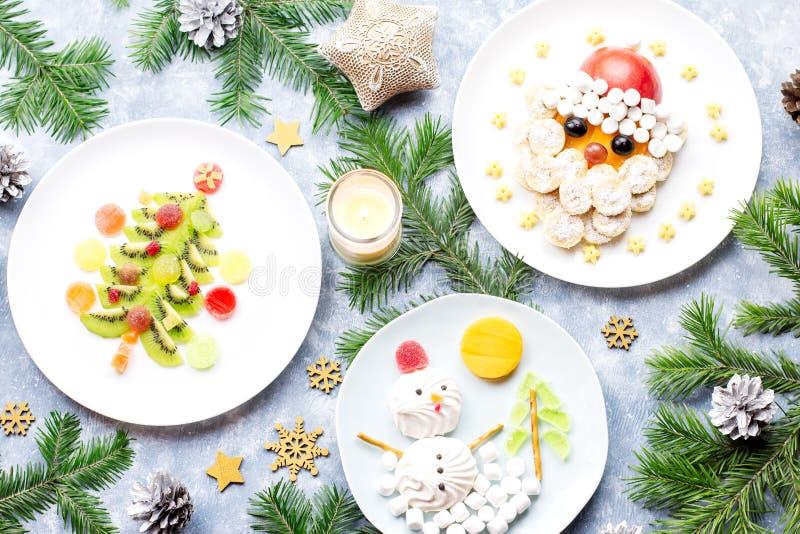 Christmas food for children - kiwi Christmas tree, marshmallow snowman, banana Santa Claus. Top view royalty free stock image