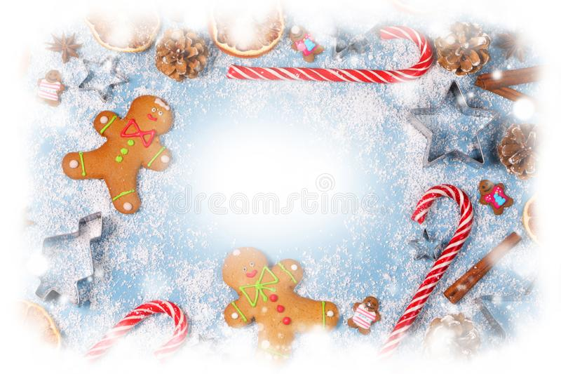 Christmas food frame. Gingerbread cookies, spices and decorations on blue background with copy space stock photo