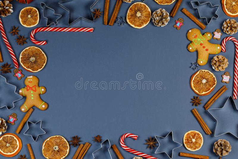 Christmas food frame. Gingerbread cookies, spices and decorations on blue background with copy space stock images