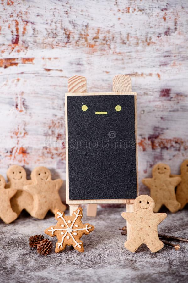 Christmas food. Gingerbread man cookies in Christmas setting with a small blackboard. Xmas dessert stock images