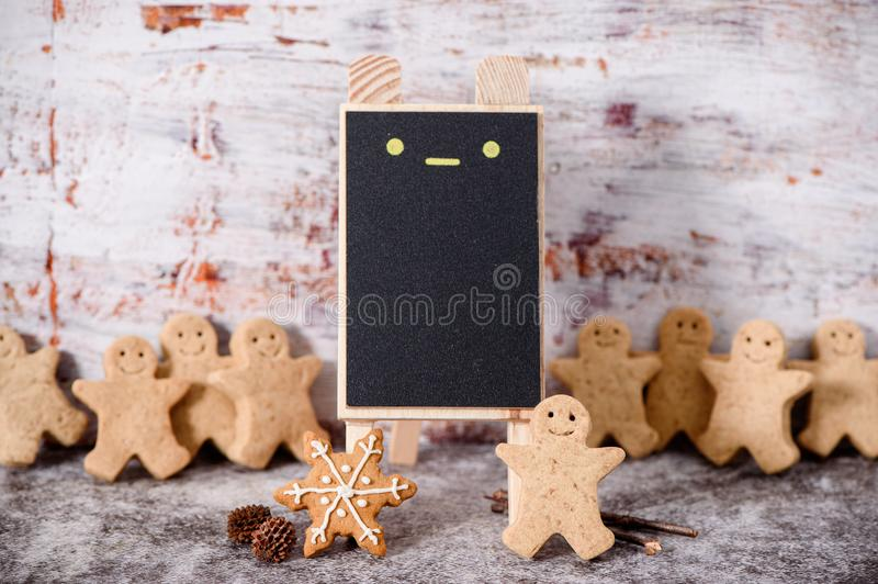 Christmas food. Gingerbread man cookies in Christmas setting with a small blackboard. Xmas dessert royalty free stock photography