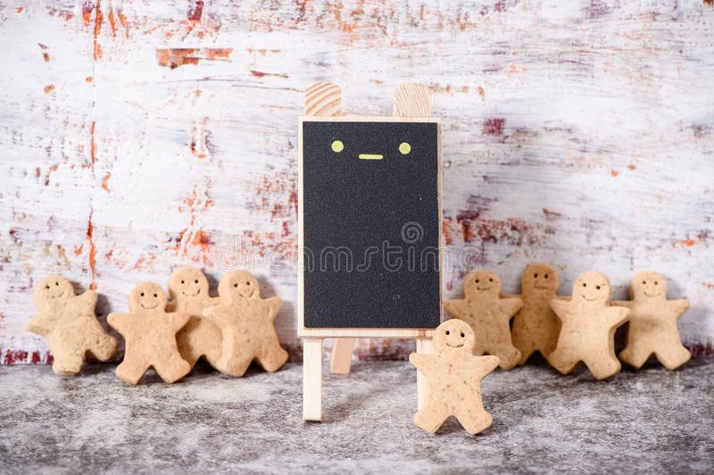 Christmas food. Gingerbread man cookies in Christmas setting with a small blackboard. Xmas dessert royalty free stock photos