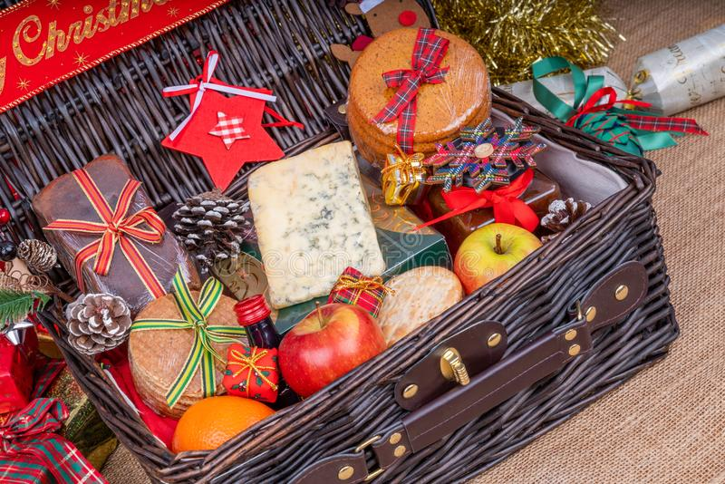 Christmas Food Hamper. Wicker Hamper loaded with Christmas Treats and Fruits royalty free stock image