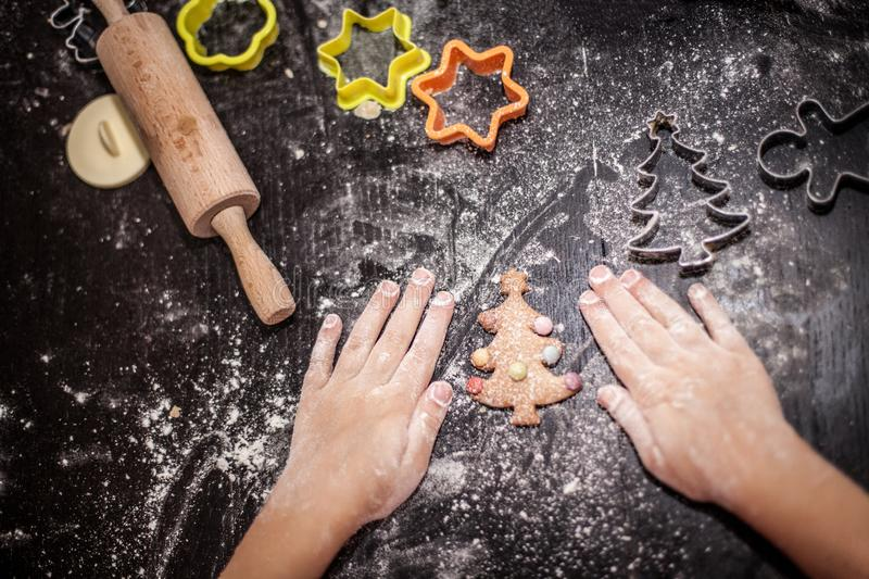 Christmas food. Homemade gingerbread cookies with ingredients for christmas baking and kitchen utensils on dark table, Family. Preparation holiday food, hands stock photos