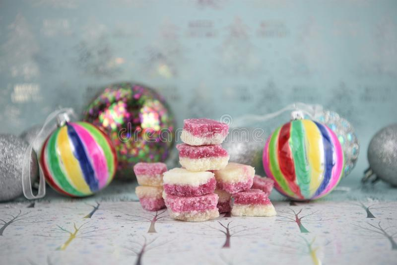 Christmas food photography picture with old fashioned English coconut ice sweets and bauble tree decorations in the background. Photograph of Christmas food stock images