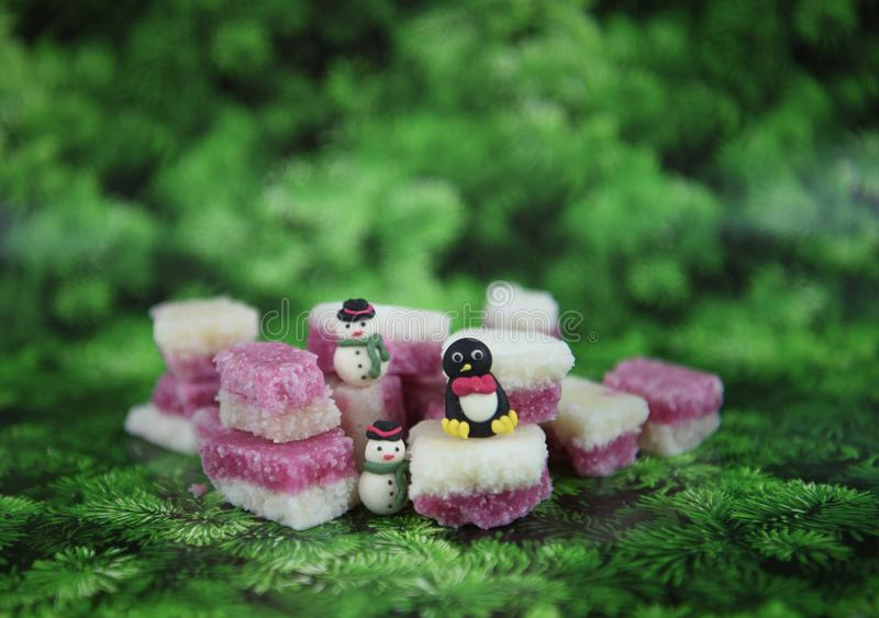 Christmas food photography picture with old fashioned English coconut ice treats with cute snowman and penguin decorations stock image