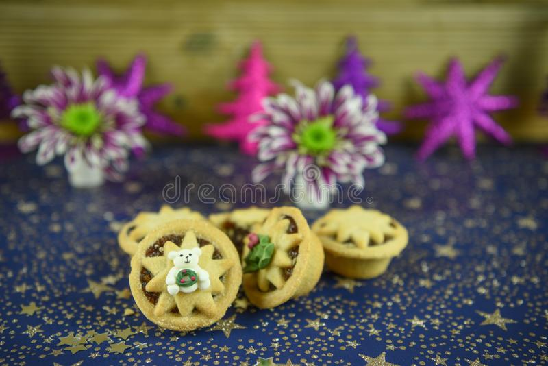 Christmas food photography picture with traditional food of mince pies with English winter flowers and polar bear iced decoration royalty free stock images