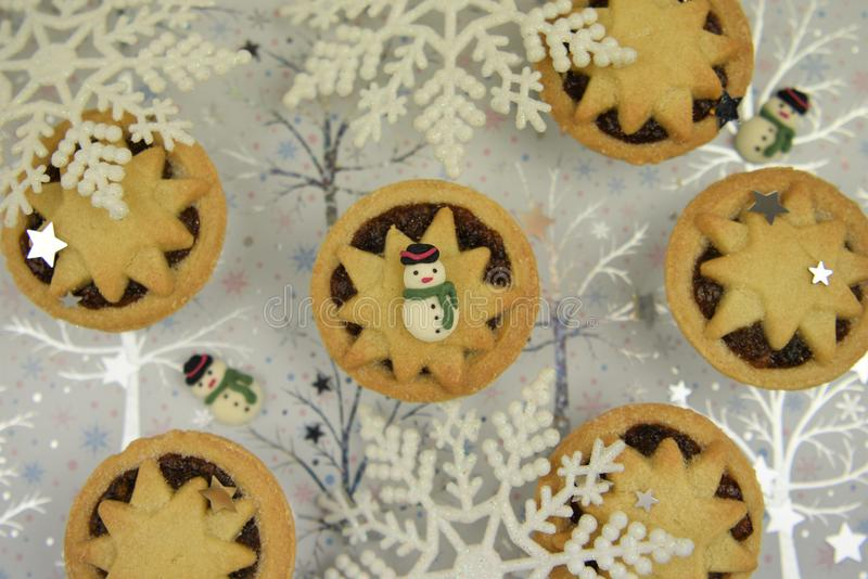 Christmas food photography picture with traditional mince pies and cute snowman decoration on white shiny snowflake background stock photo