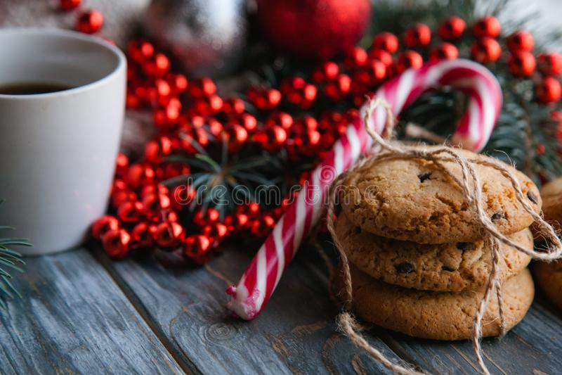Christmas food snack cookies tea red bead string. Christmas festive food snack concept. pile of chocolate chip cookies and a mug of tea on wooden background. red stock images