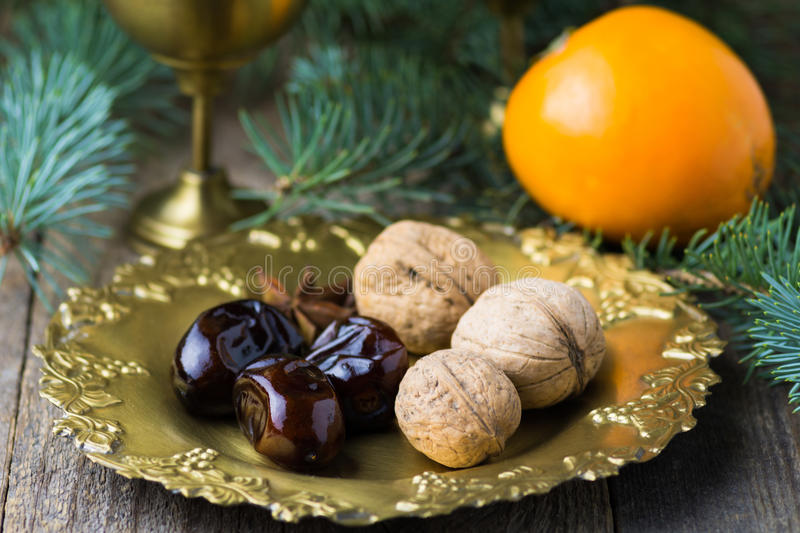 Christmas food still life: arabic dates, walnuts, persimmon. Food still life in arabic style: dried dates, whole walnuts, spices and persimmon on vintage golden stock photos
