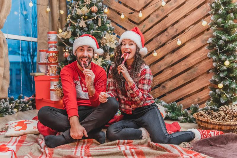 Full-body photo of young people in red clothes and Santa hats, tasting yummy candycanes in christmas atmosphere. stock photos
