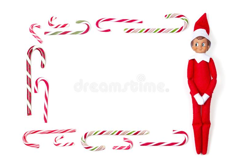 Christmas frame background. Many candy canes and little toy Santa elf on white background. Top view. Christmas frame background. Many candy canes and little toy royalty free stock photos