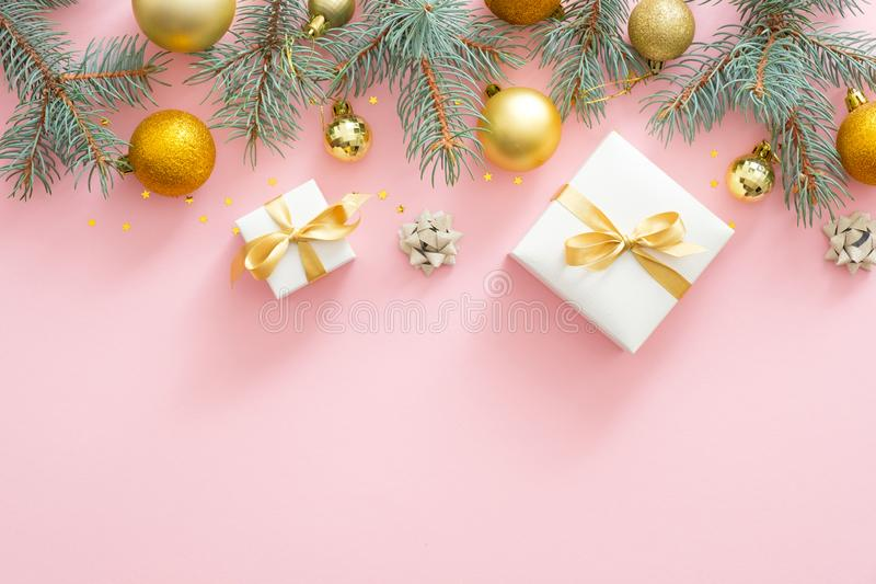 Christmas frame border with fir tree branches, Christmas golden balls, presents on pastel pink background. Flat lay, top view royalty free stock images
