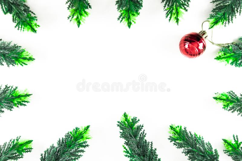 christmas frame or border from green pine leaves and red ball in white background stock photography