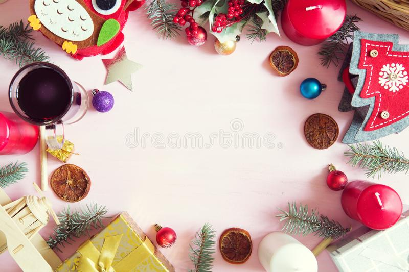 Christmas frame or border with a large assortment of christmas prop, decorations, balls, gifts and candles on a pink wooden backgr stock images