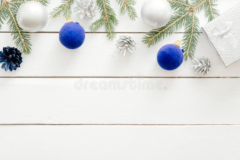 Christmas frame border made of blue and silver decorations, balls, gift boxes, pine tree branch on white wooden background. Flat royalty free stock photos