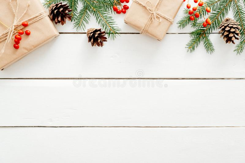 Christmas frame border made of fir tree branches, gift boxes, red berries, pine cones on rustic wooden white desk. Christmas royalty free stock photo