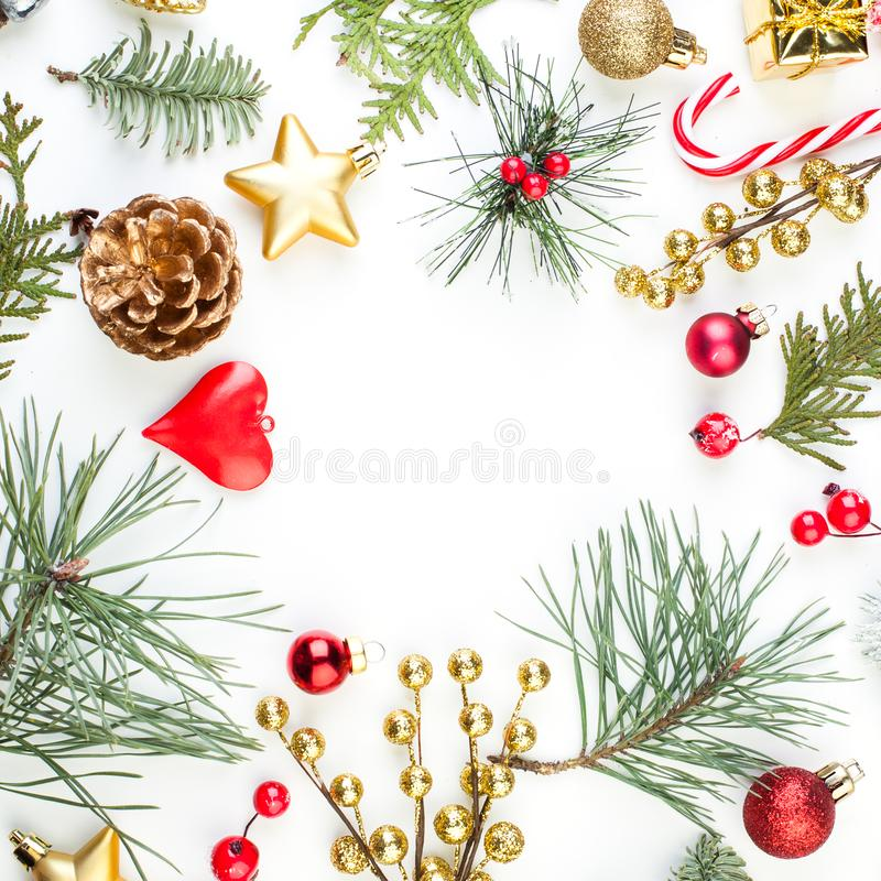 Christmas frame border with Xmas decor on white background. Green Xmas tree twig, red glass balls, berries, candy food and gold. Stars decoration stock images