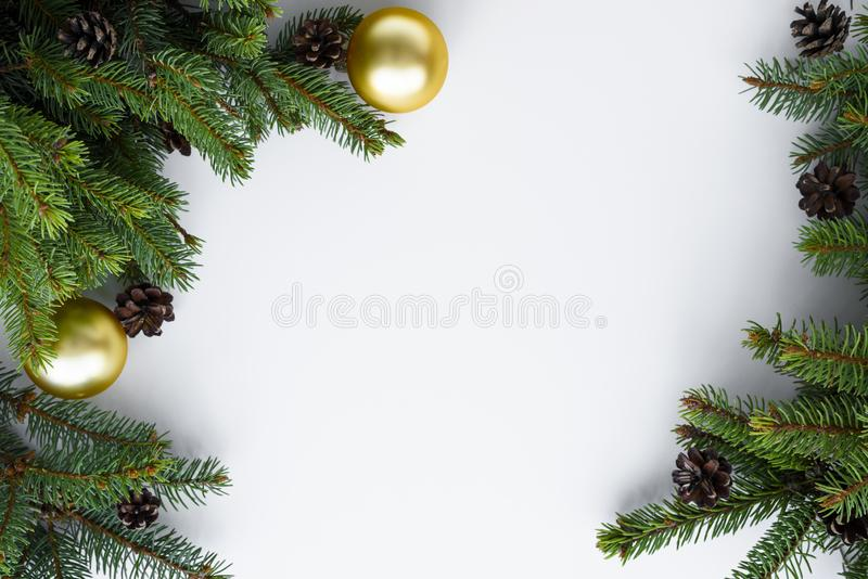Christmas frame with copy space for happy holidays wishes. Evergreen tree branches, cones and gold baubles. Christmas frame with copy space for happy holidays royalty free stock photos