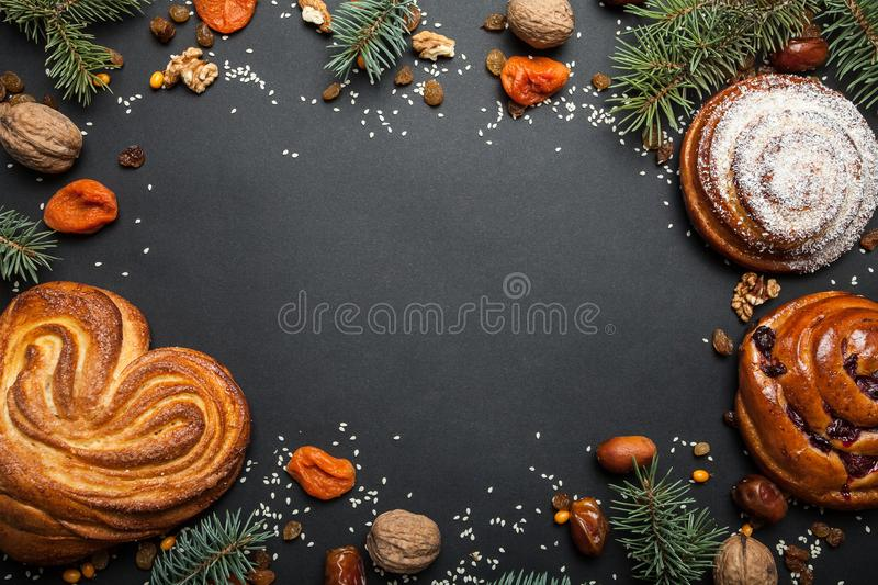 Christmas frame from edible ingredients, sweet buns, nuts, dried fruits, pine needles, space for text. Copy space.  stock image