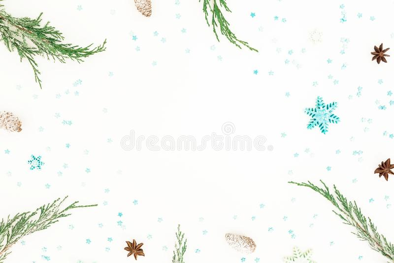 Christmas frame of evergreen tree branches, blue snowflakes and pine cone on white background. Flat lay, top view. Winter concept stock photo