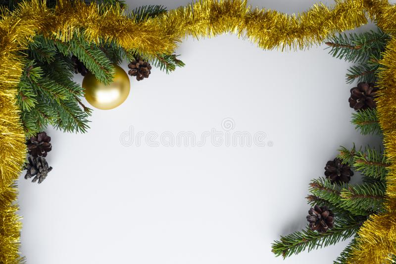 Christmas frame. Festive decorations such as gold tinsel and baubles, conifer tree branches and cones. Copy space for wishes. Christmas frame created with stock photo