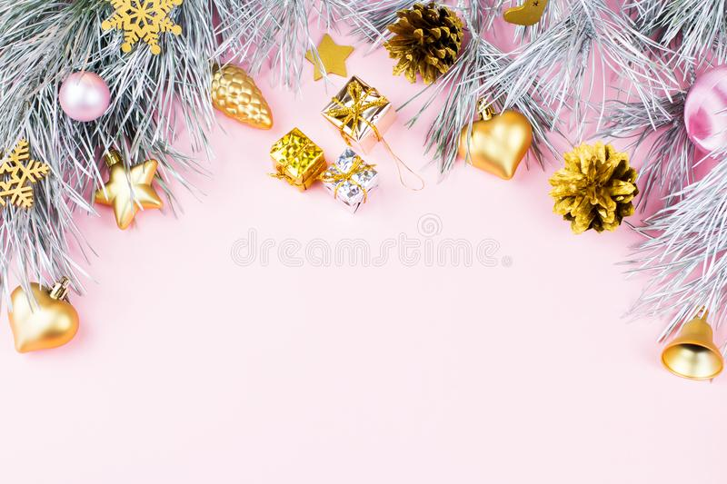 Christmas frame with fir branches, conifer cones, christmas balls and golden ornaments on pastel pink background stock photography