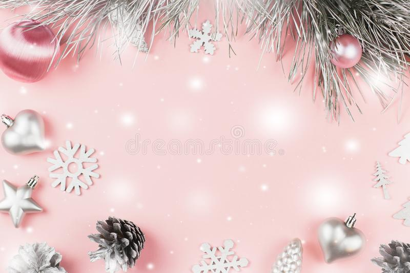 Christmas frame with fir branches, conifer cones, christmas balls and silver ornaments on pastel pink background royalty free stock image