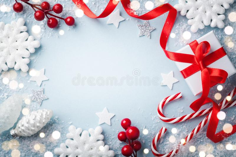 Christmas frame, greeting card. Gift or present box and holiday decoration on blue background top view. Happy New Year composition royalty free stock photos