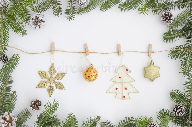 Christmas frame made of christmas tree fir branches. Oon the rope with clothespins hanging toys, a star, New Year`s toys stock photos