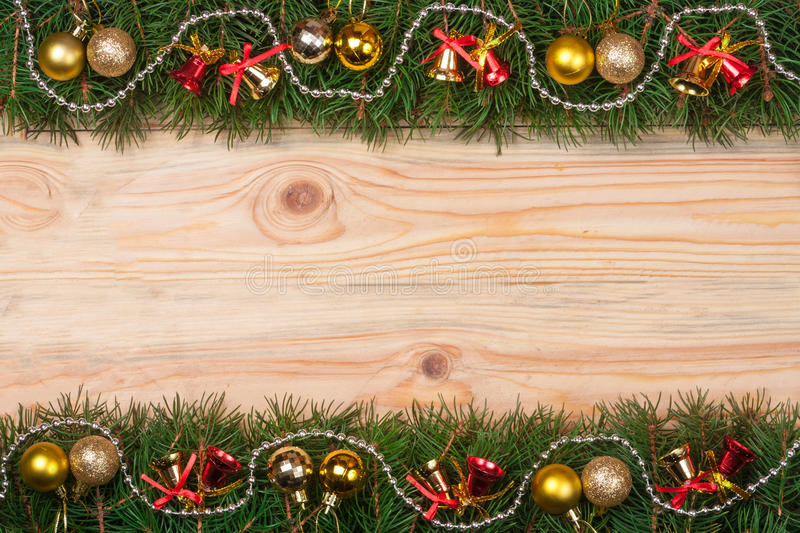 Christmas frame made of fir branches decorated with bells beads and golden balls on a light wooden background.  royalty free stock photography