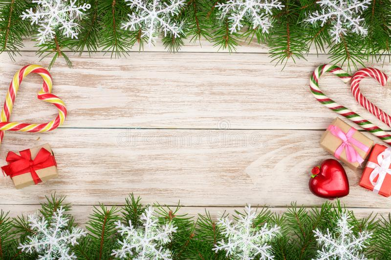 Christmas frame made of fir branches decorated with snowflakes candy canes and boxes on a light wooden background stock photos