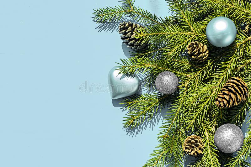 Christmas frame made of fir branches, festive decorations on blue wooden table. Christmas background. Flat lay. Top view royalty free stock image