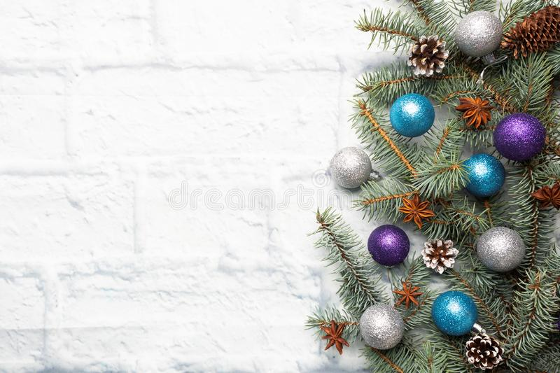 Christmas frame made of fir, Christmas tree decorations in silver and blue on a light brick background. Copy space. Flat lay stock images