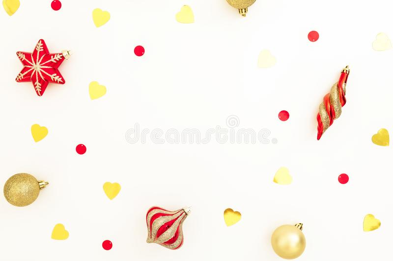 Christmas frame made of golden and red decorations with confetti on white background. Flat lay, top view, copy space stock image