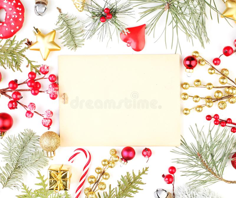 Christmas frame made of Xmas decorations and vintage paper card. Golden gift, star, red holly berries and green fir branch royalty free stock photography