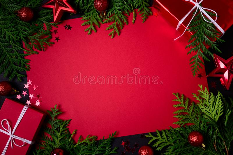 Christmas frame of red gift boxes, fir branches, confetti, paper for text and toys on black background. Flat lay. Top view. Copy stock photography