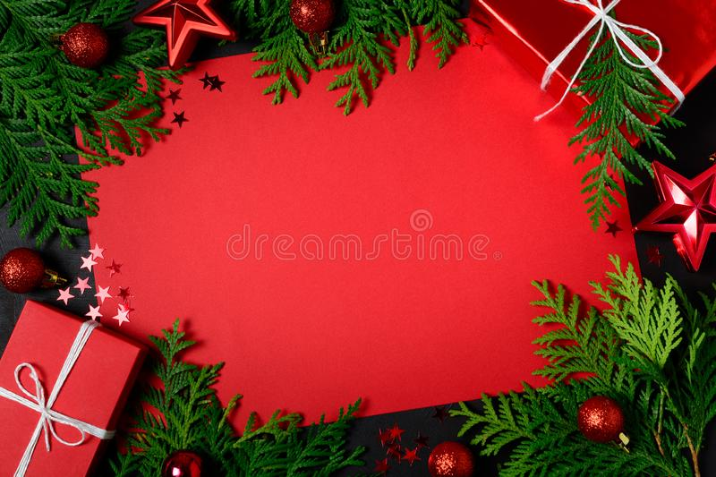 Christmas frame of red gift boxes, fir branches, confetti, paper for text and toys on black background. Flat lay. Top view. Copy stock images