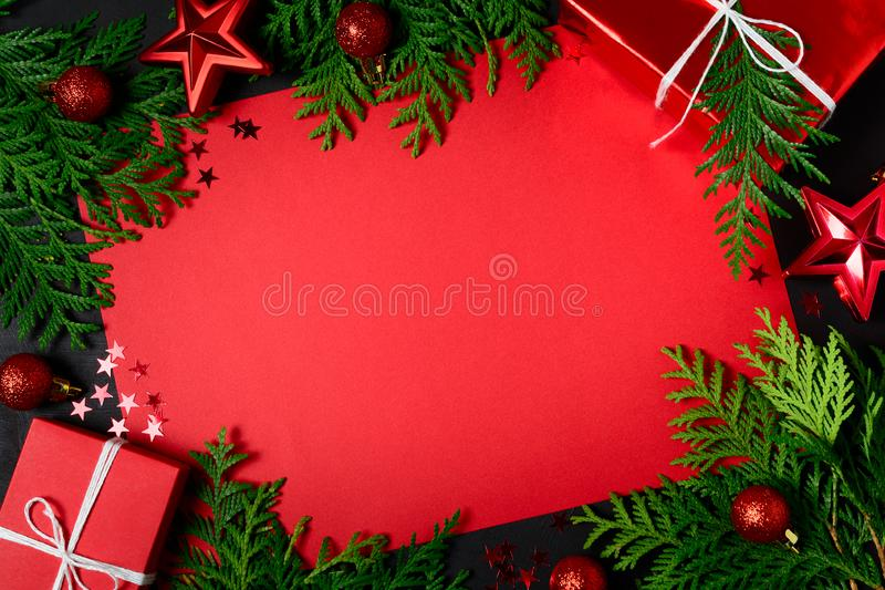 Christmas frame of red gift boxes, fir branches, confetti, paper for text and toys on black background. Flat lay. Top view. Copy stock photo